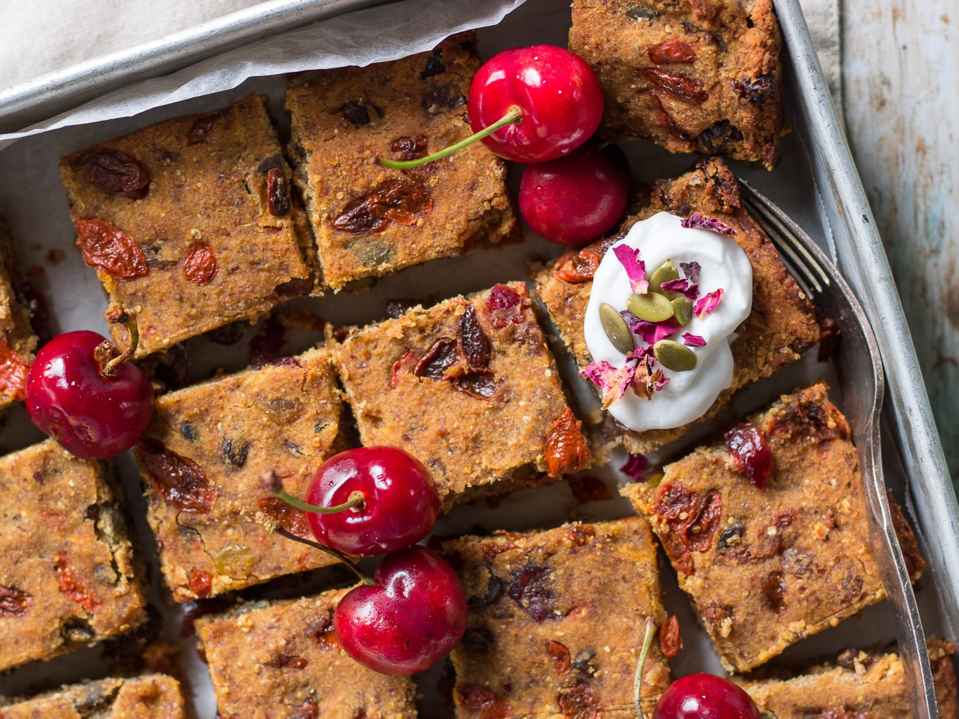 Nut Free Vegan Fruit Slice in baking tray topped with coconut yoghurt and fresh cherries!