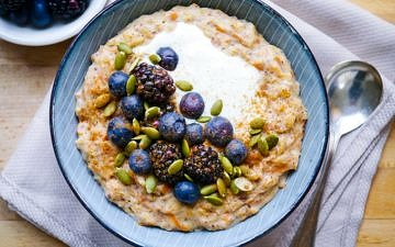 Carrot cake porridge in blue bowl with blueberries and pumpkin seeds