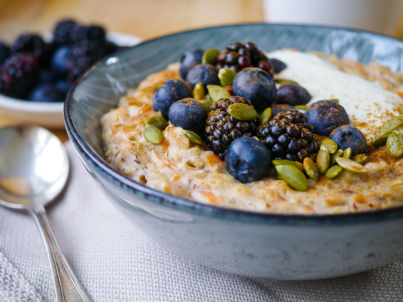 Healthy Carrot Cake Porridge in a blue bowl topped with blueberries and pumpkin seeds