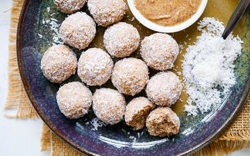 Protein balls rolled in desiccated coconut on a blue ceramic plate