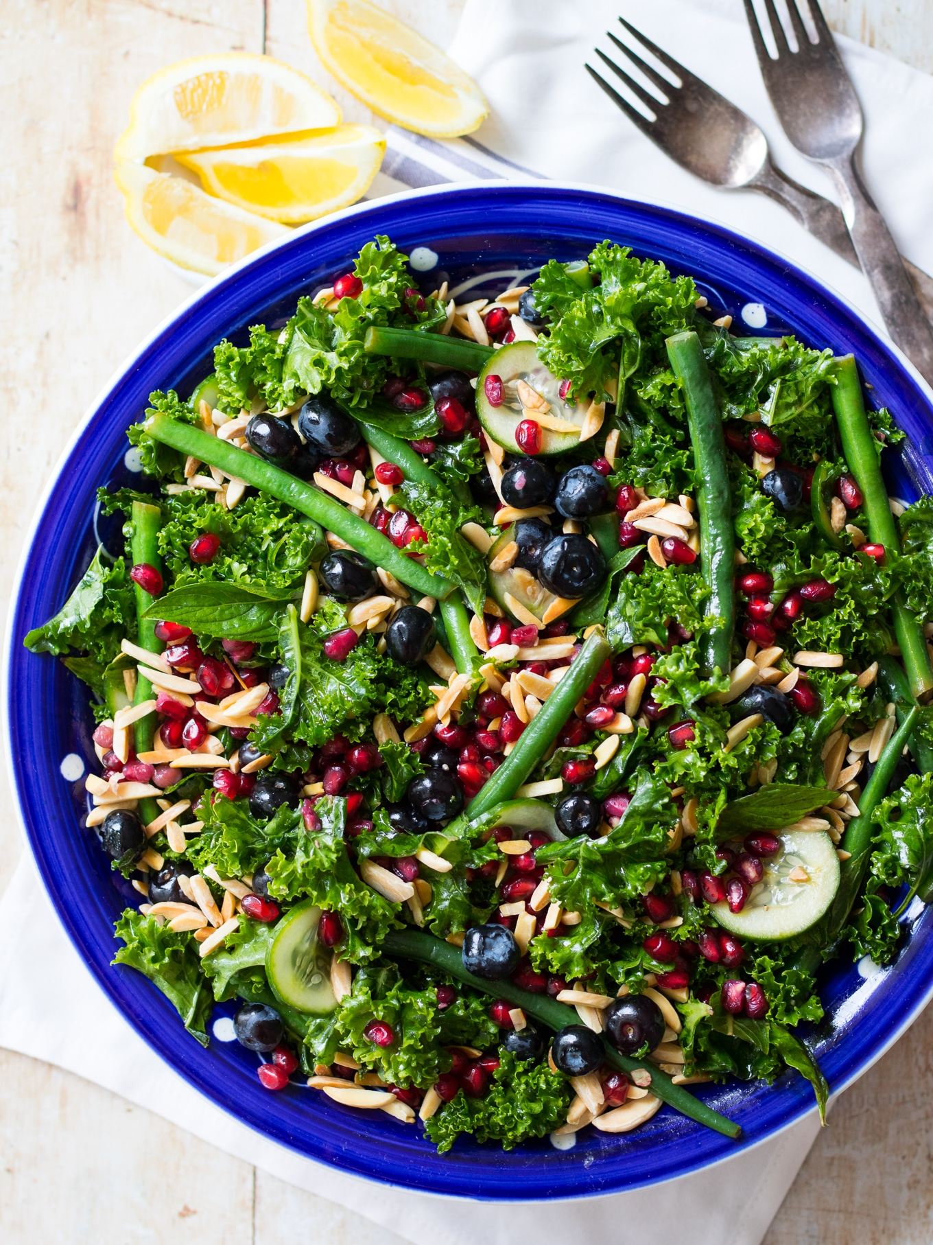 A summery blueberry kale salad filled with vibrant healthy greens, blueberries, pomegranate and crunchy toasted almonds. Perfect for sharing at a BBQ or any dinner party! Gluten free, dairy free, grain free and paleo. #kalesalad