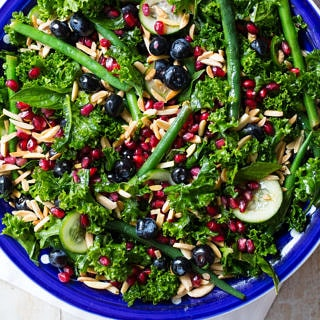 Summery blueberry kale salad featuring massaged kale, green beans, cucumber, mint, blueberries, pomegranate and toasted almonds. Yum!