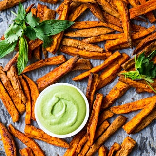 Cinnamon Paprika Sweet Potato Fries roasted on a baking tray, with dipping sauce and fresh mint.