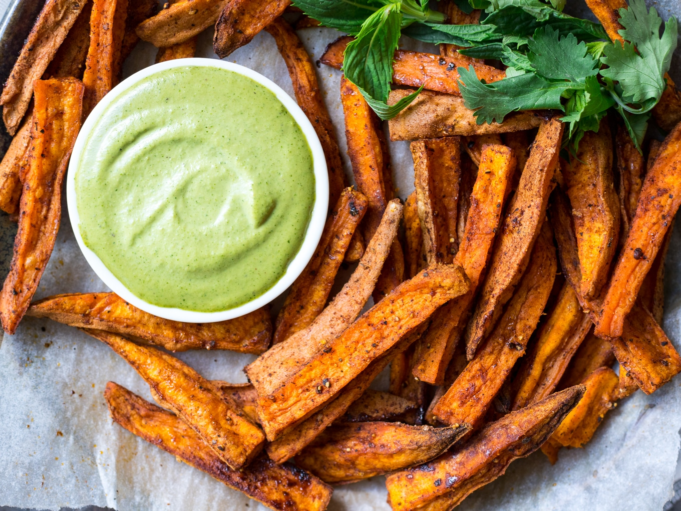 Cinnamon Paprika Sweet Potato Fries arranged on a plate with dipping sauce and herbs.