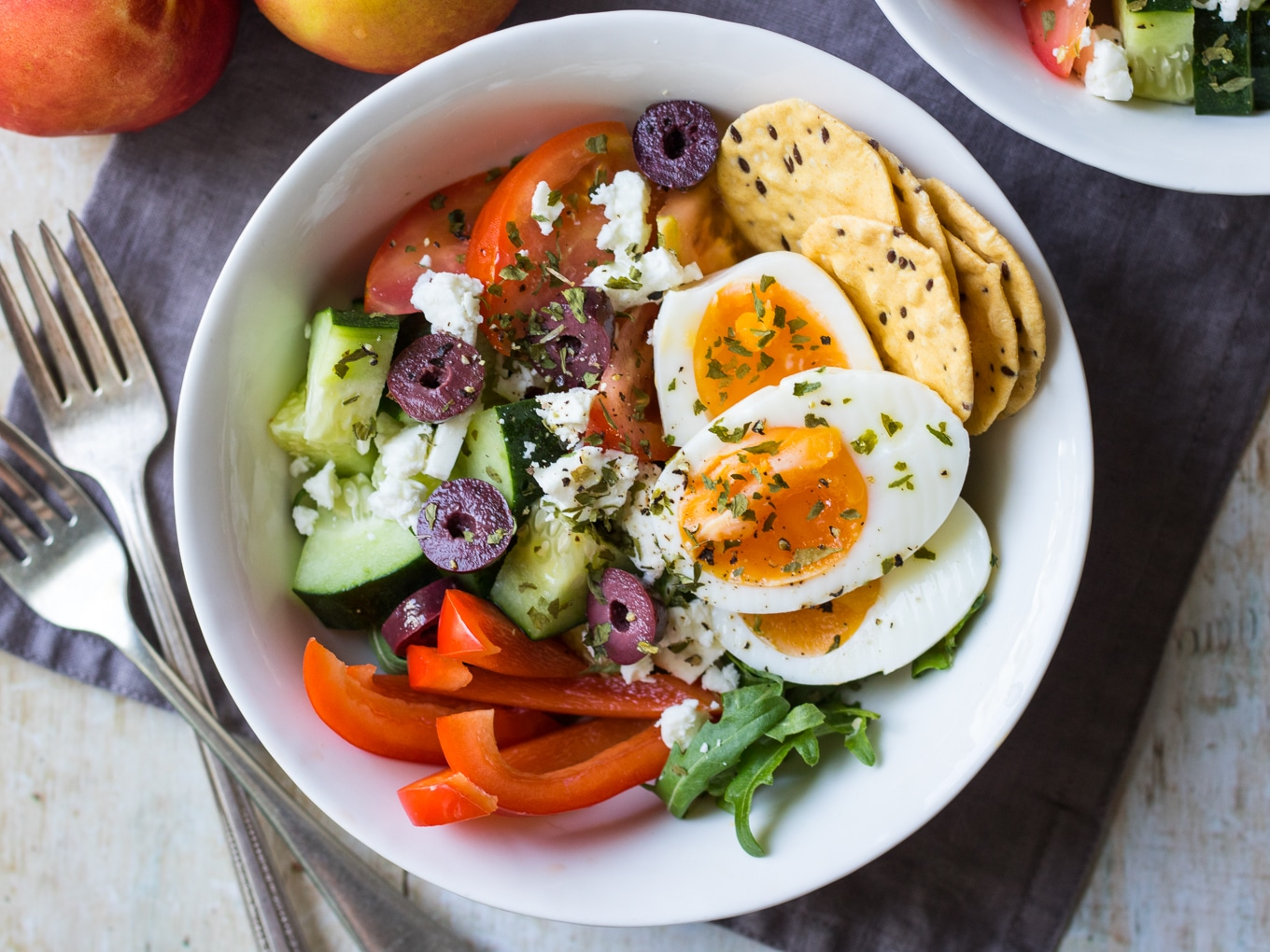 Meal prep breakfast bowls Greek style. Healthy breakfast salad pots featuring sliced boiled eggs with rocket, cucumber, tomatoes, capsicum, feta, olives, herbs and extra virgin olive oil.