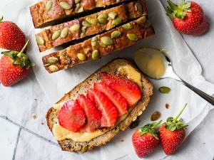 Slices of apple zucchini snack cake from top down, one flat topped with sliced strawberries