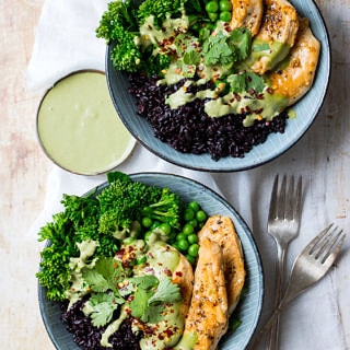 Chicken black rice bowls; two blue bowls filled with black rice, chicken and broccolini, side of green herb sauce, on a light table