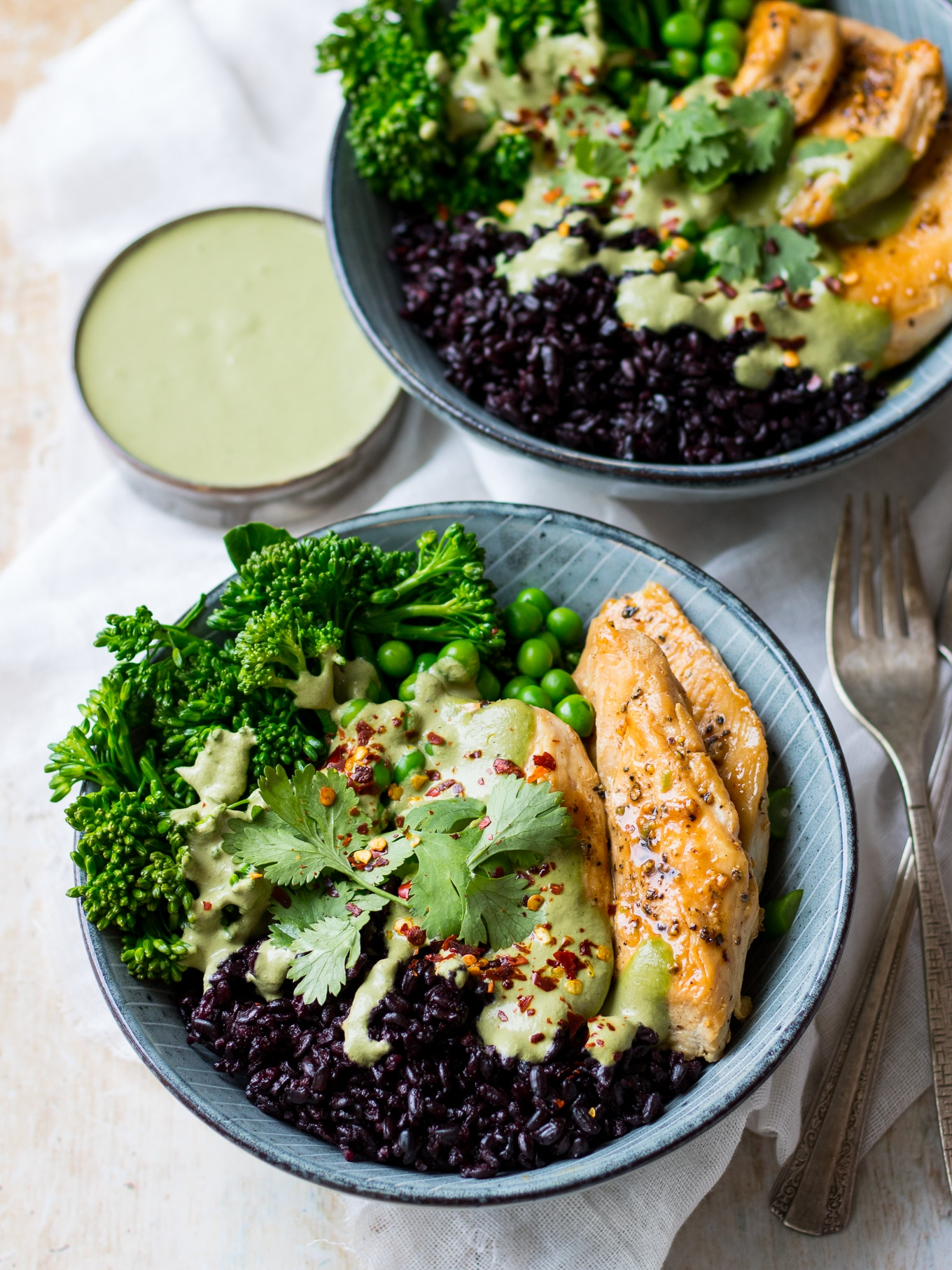 Blue bowls, chicken black rice bowls, layered with black rice, marinated chicken, peas, broccolini, green cashew herb sauce