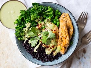 Chicken black rice bowl, one blue serving bowl filled with rice, marinated chicken, broccolini, peas and creamy herb sauce