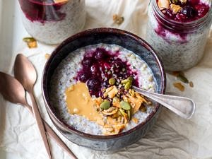 Buckwheat bircher in a small blue ceramic bowl, berries, nut butter and granola on top