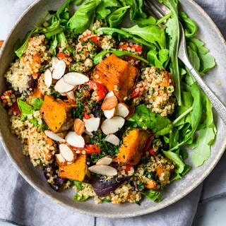 Roast pumpkin quinoa salad close up in grey shallow bowl, fork nestled in side