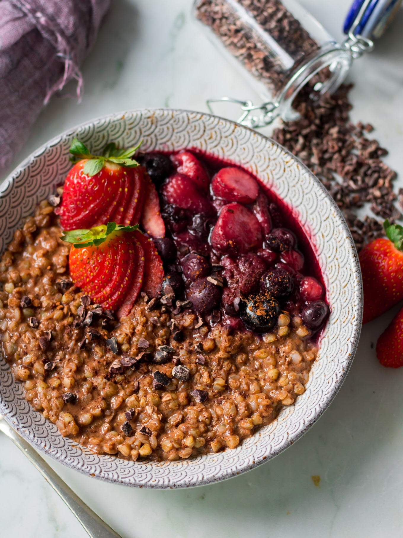 Angle view of chocolate buckwheat porridge in patterned bowl, scattered cacao nibs, berries on top