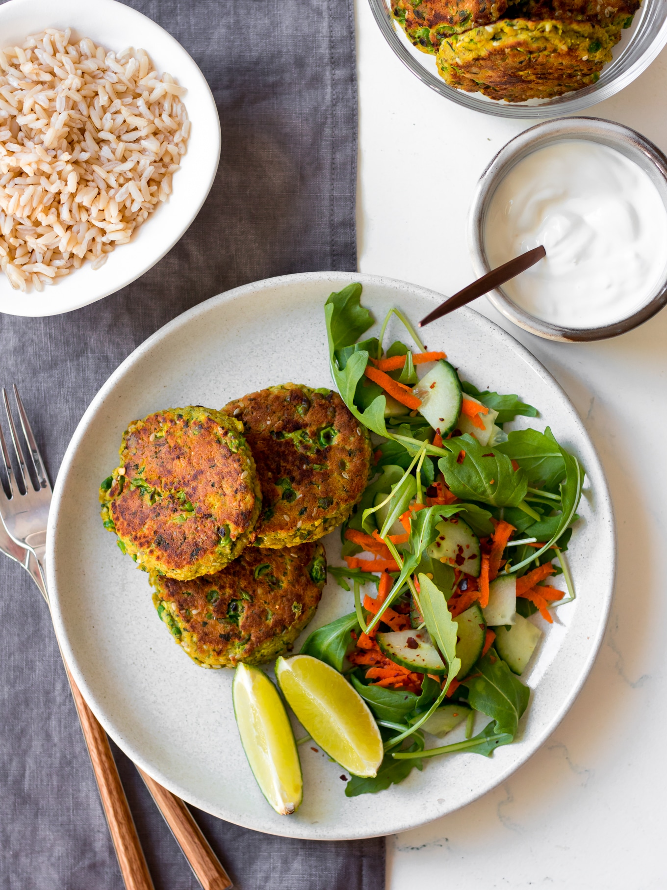 thai salmon cakes on white plate with side salad and lime