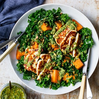 Halloumi kale salad in grey ceramic bowl, pesto sauce, wooden table top