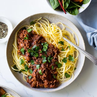 Red Wine Bolognese in ceramic bowl, spaghetti, parsley garnish