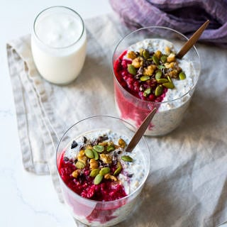 raspberry kefir overnight oats with glasses, topped with nuts, seeds, cacao nibs