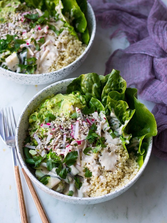 vegan protein buddha bowls with green vegetables, avocado smash, quinoa in white speckled bowls