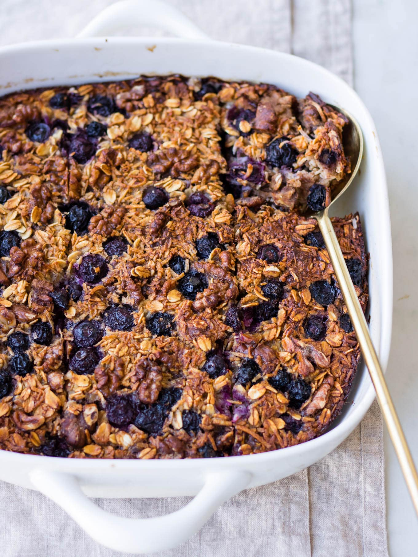 coconut blueberry baked oats in white square baking dish