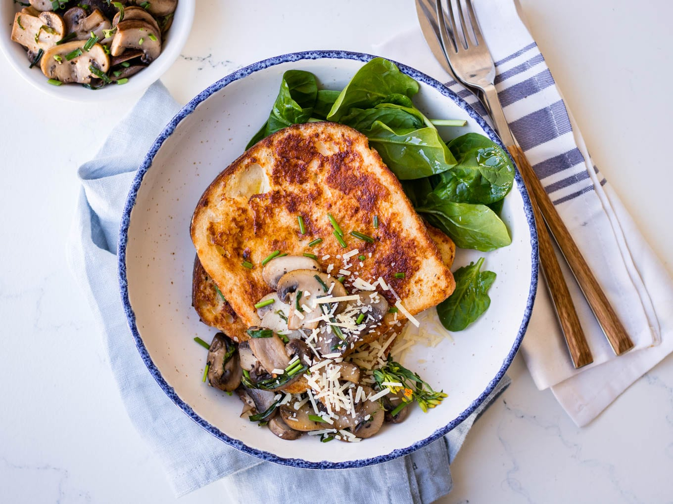 Savoury french toast with mushrooms and grated parmesan, white bowl