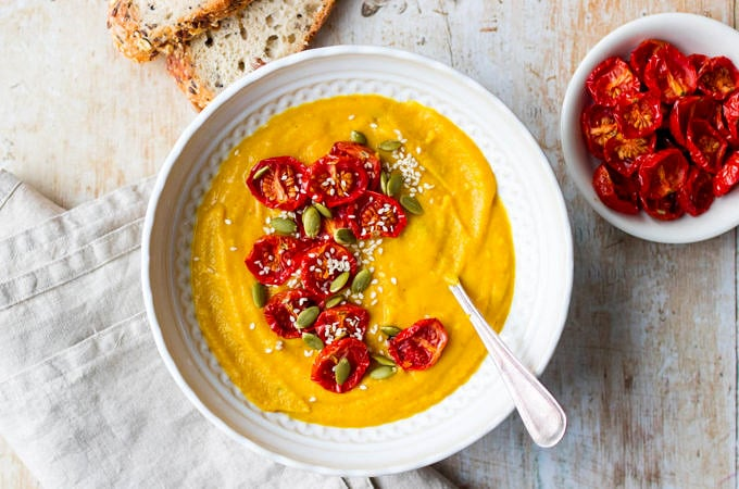 Cauliflower, sweet potato and red lentil soup in white patterned bowl with bread