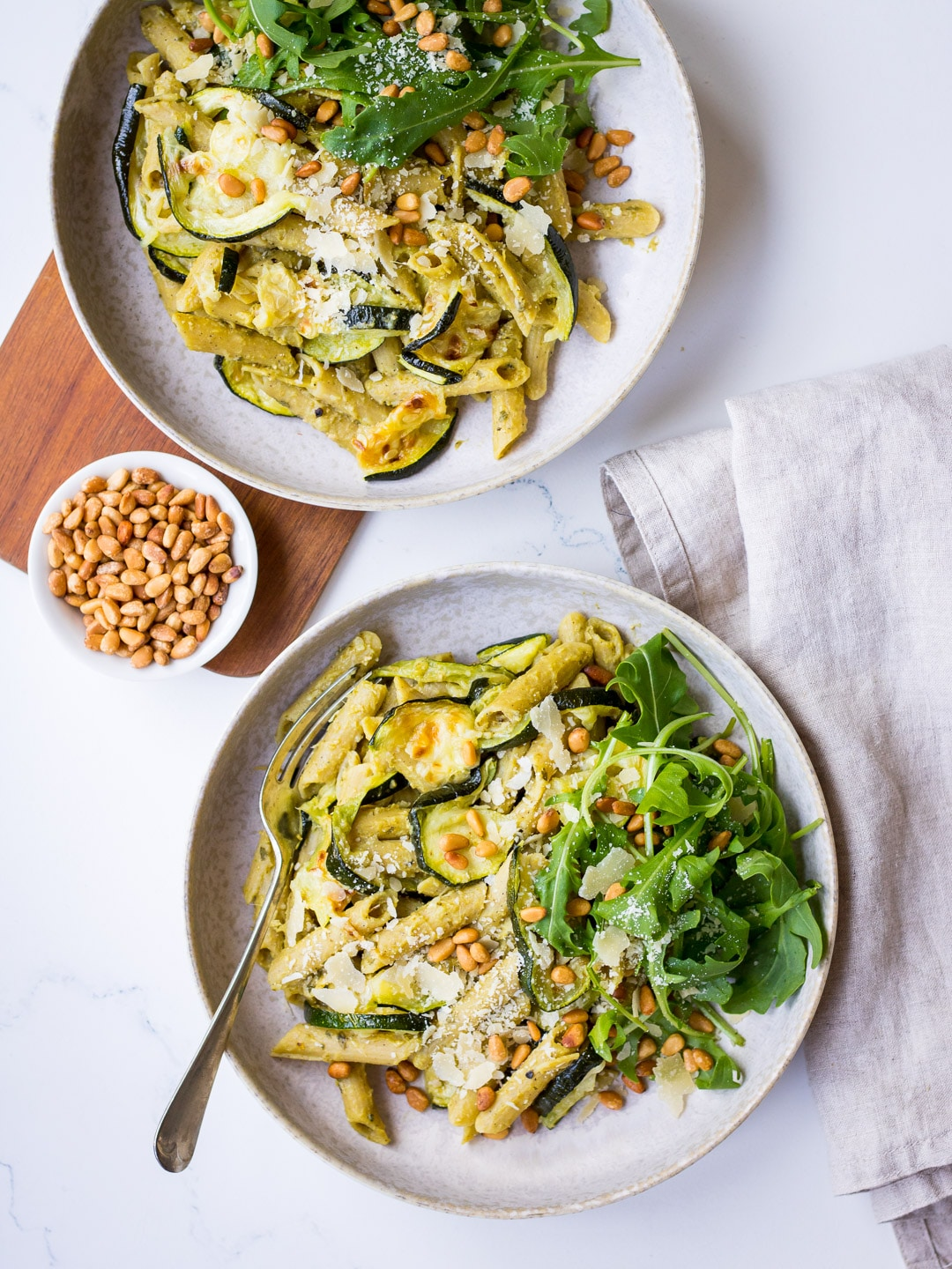 Pesto Pulse Pasta with Roasted Zucchini served in a grey ceramic bowl, with pine nuts