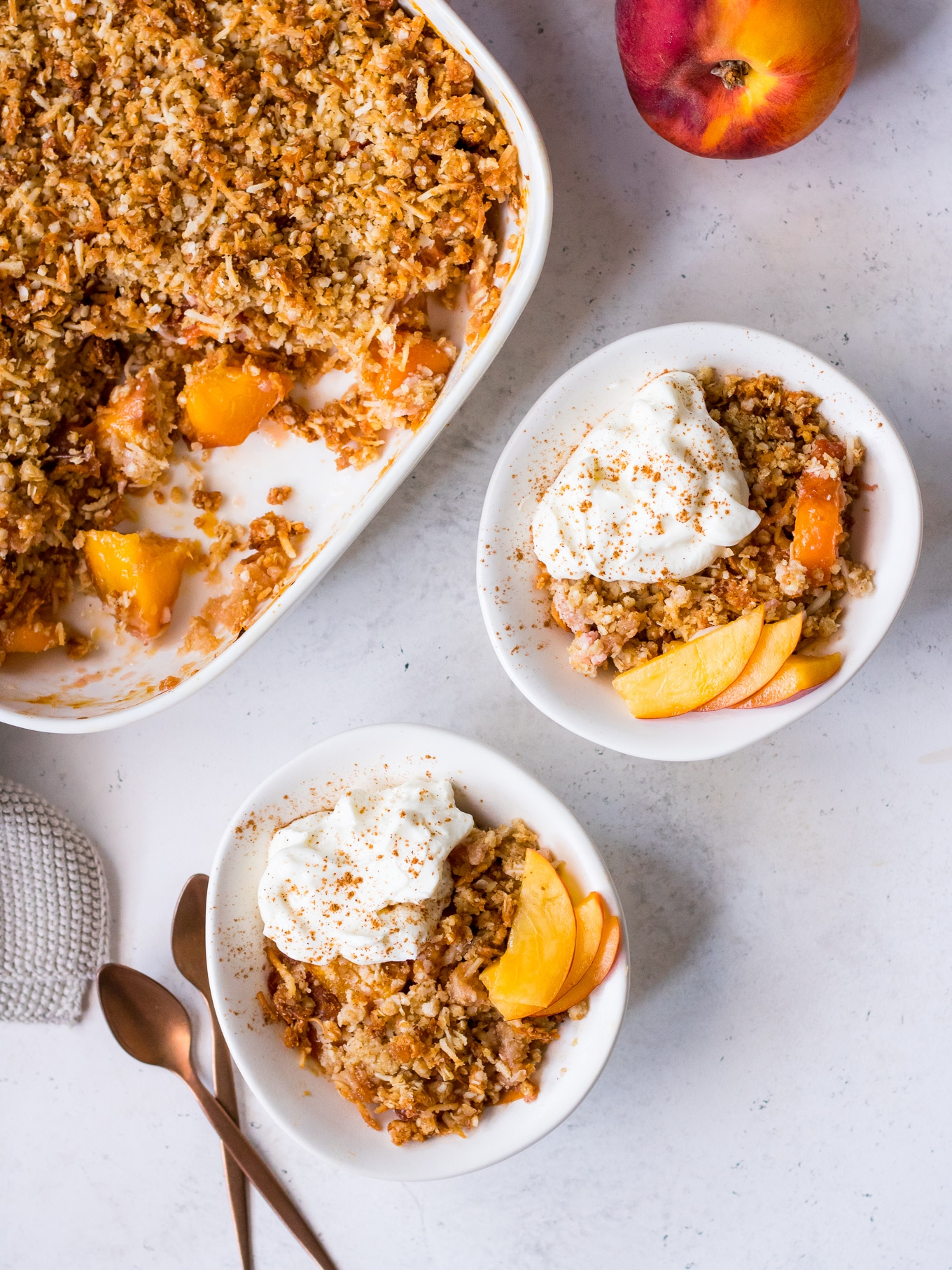 Small bowls of gluten free stone fruit crumble topped with nectarine slices and yoghurt
