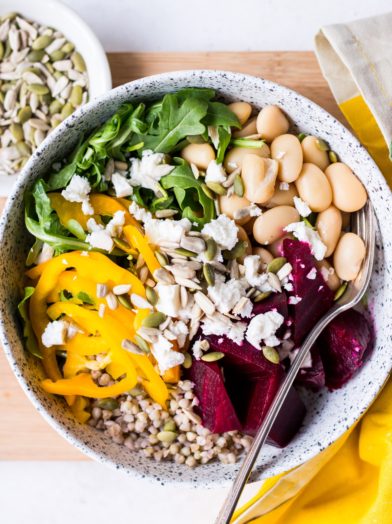 Close up of buddha bowl with roasted beetroot, feta, butter beans and seeds