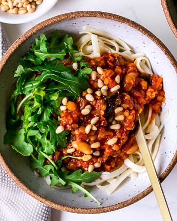 Vegan bolognese sauce topped with pine nuts
