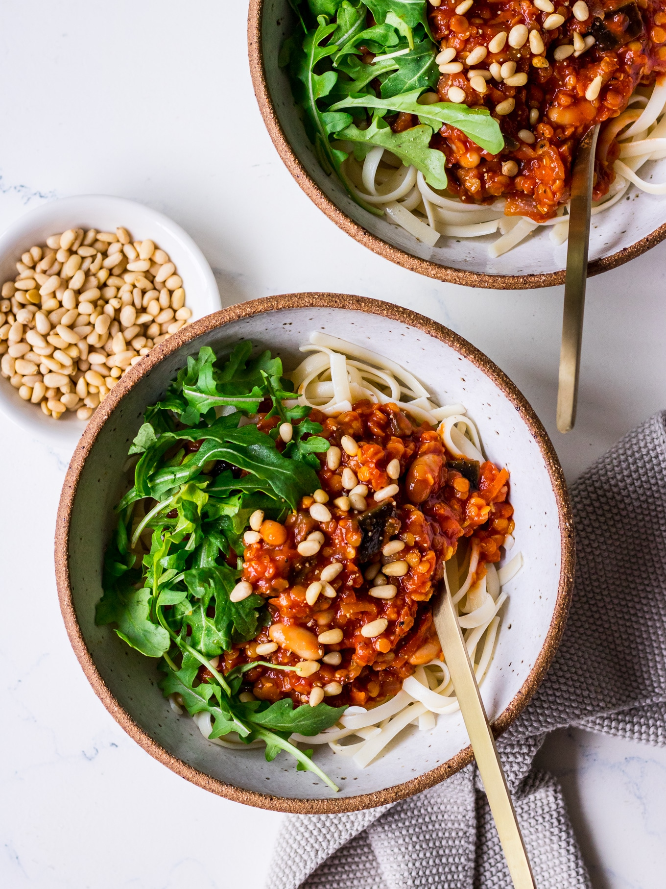 Bowls of pasta with vegan red lentil bolognese sauce and greens (Nourish Every Day)