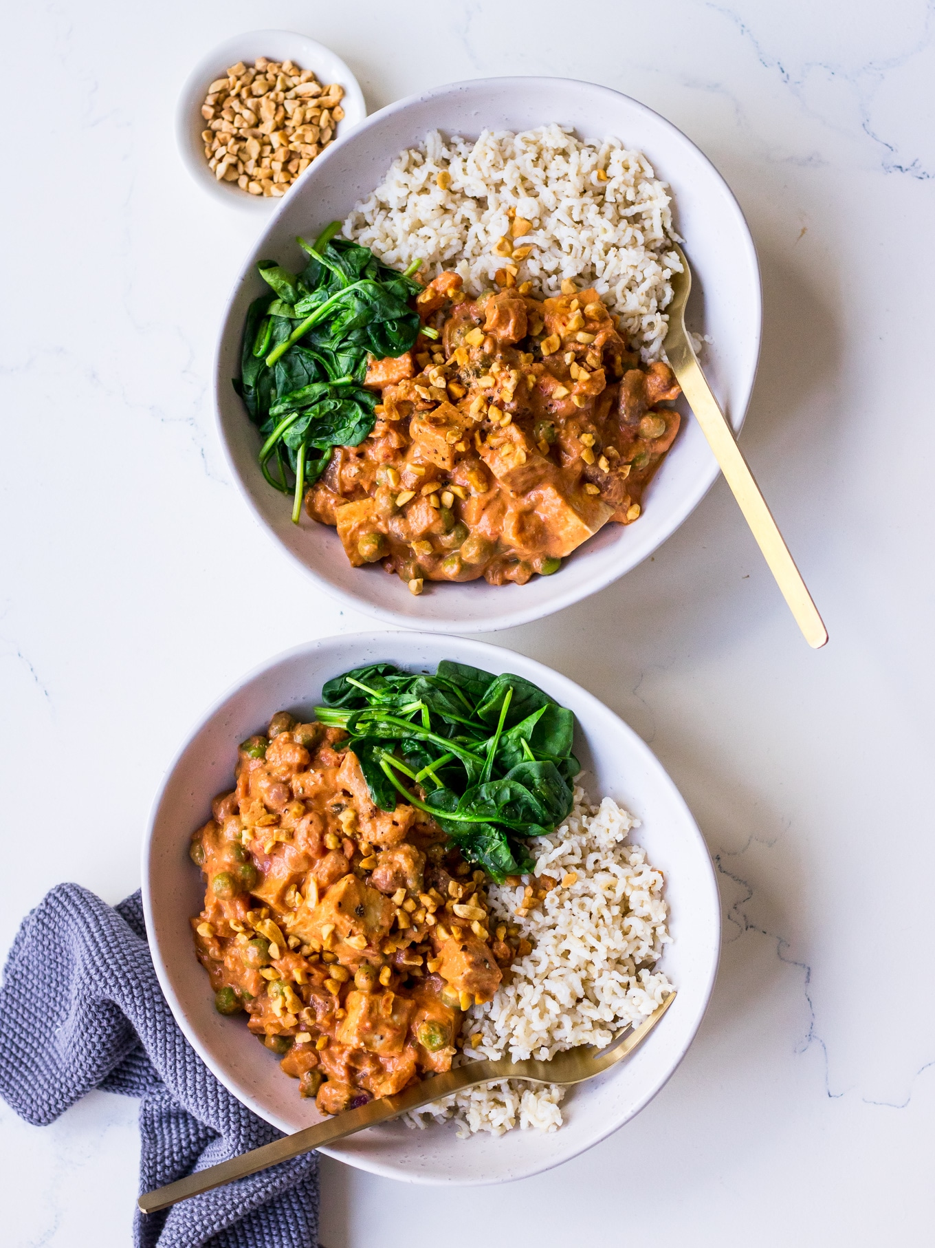 Two bowls with vegetarian curry, brown rice and spinach