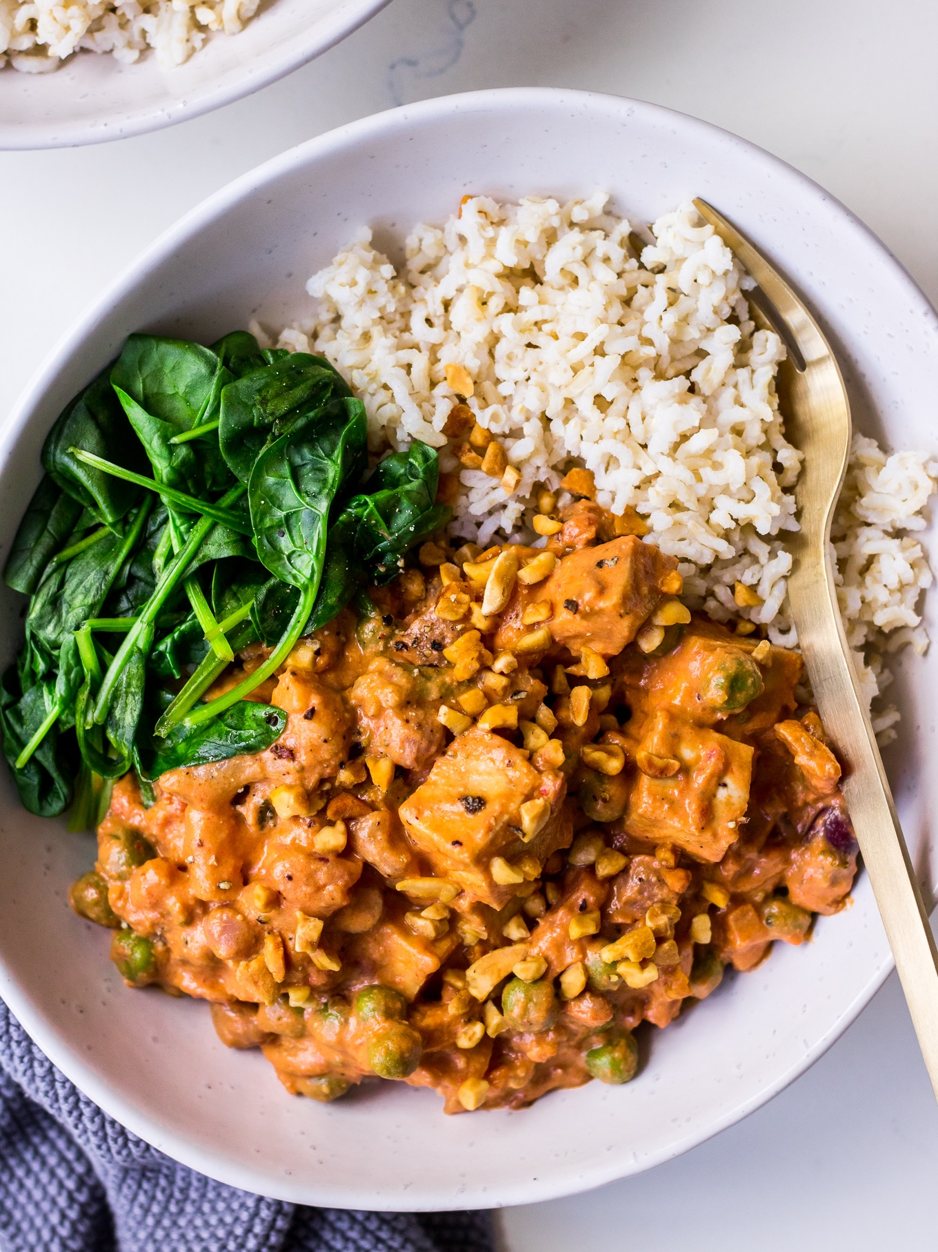 Bowl with peanut tofu curry, spinach and brown rice