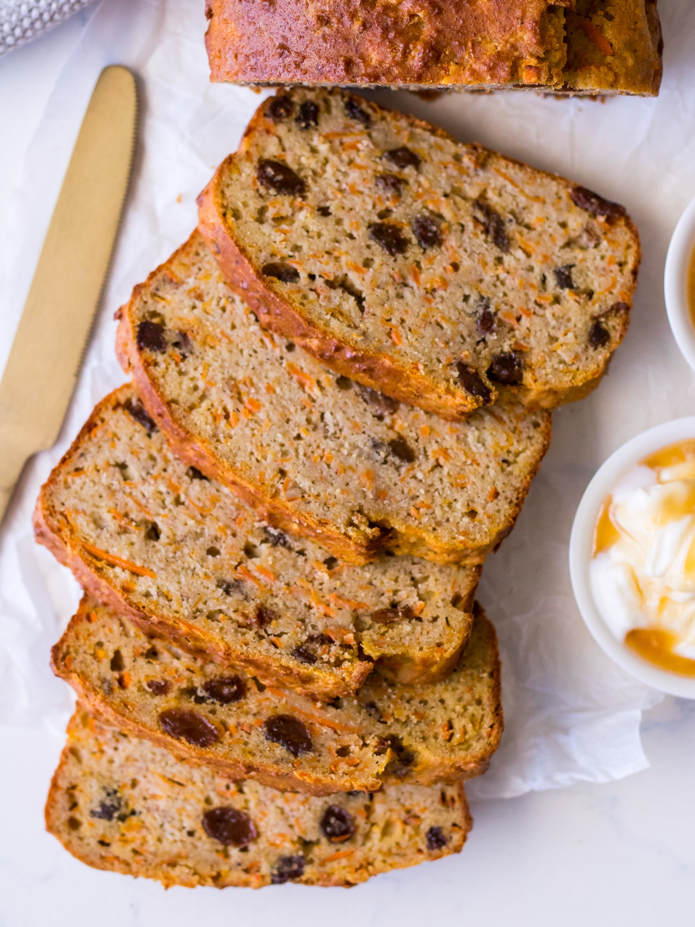 Slices of banana, carrot and sultana loaf cake against a white background