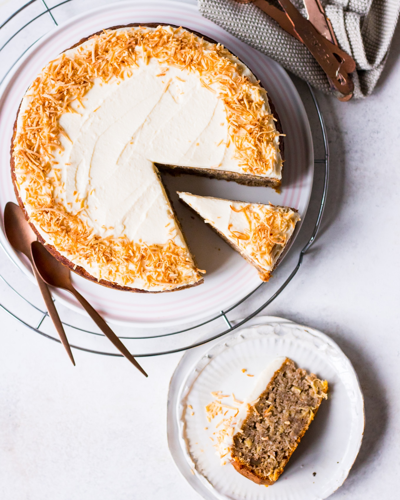 Flatlay of hummingbird cake with slice on plate, shredded coconut on frosting