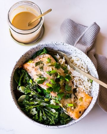 Tahini Miso Salmon in speckled white bowl with sauce jar