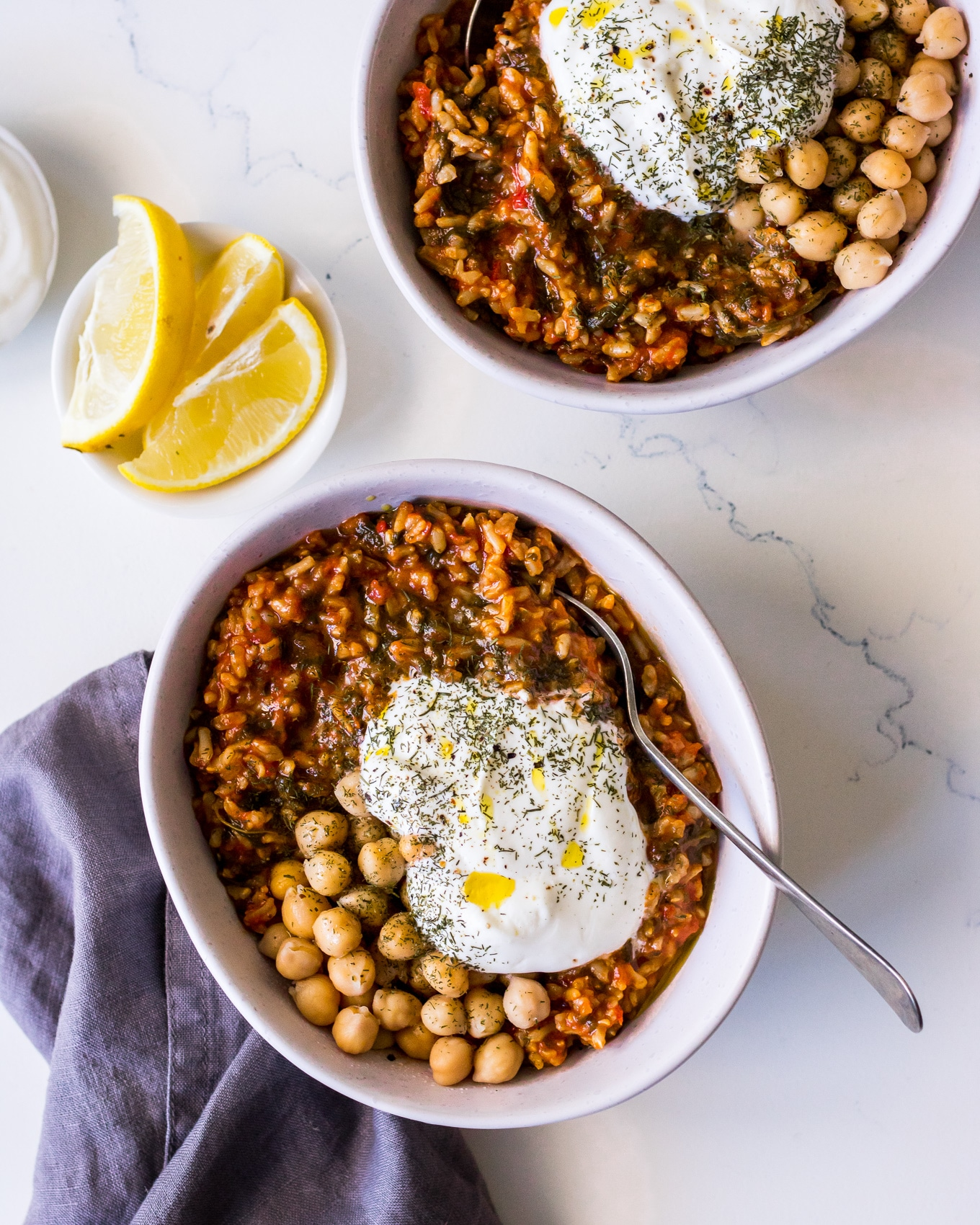 Spanakorizo (Greek spinach and rice) in a white bowl with chickpeas, yoghurt, lemon and herbs