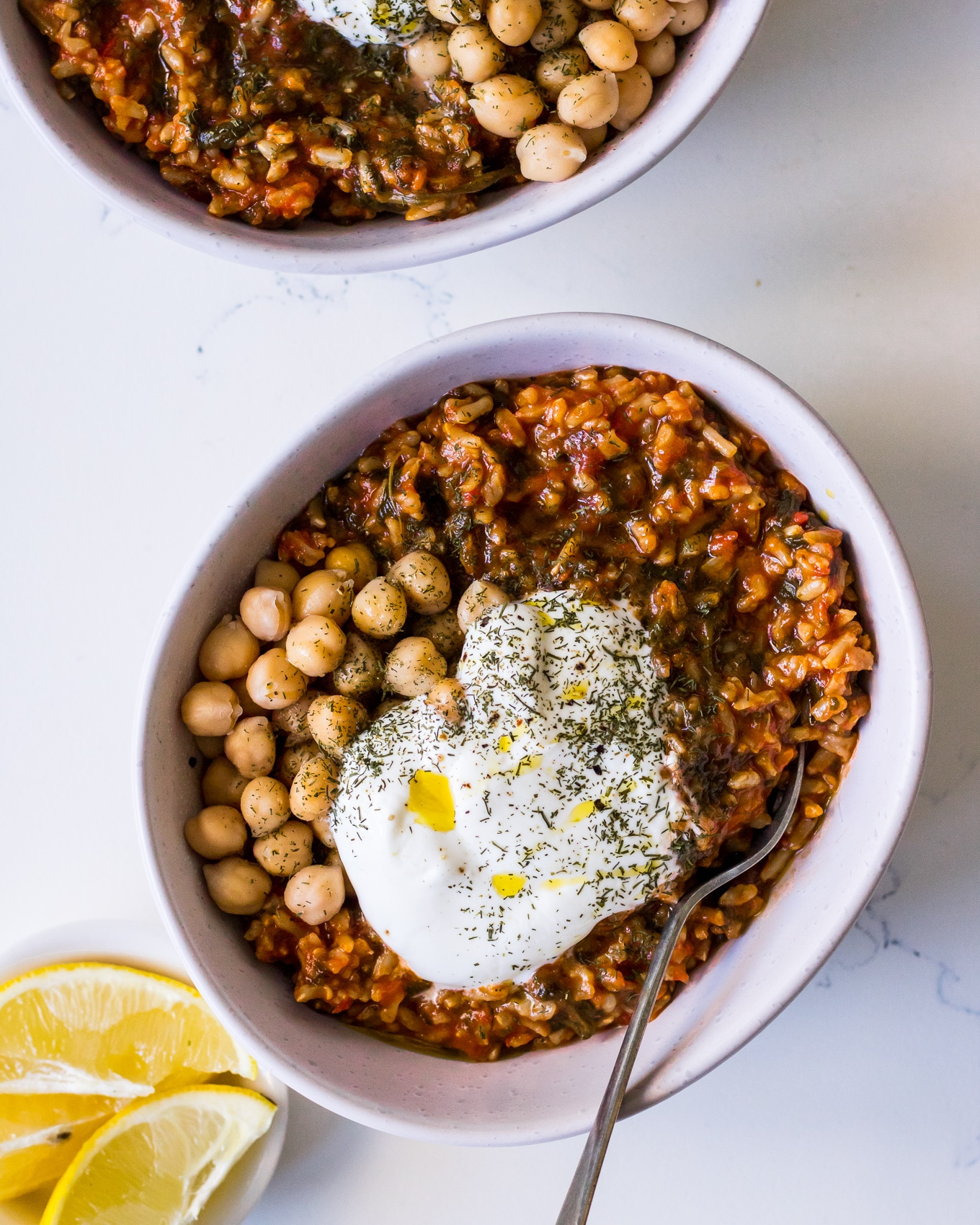 White bowl filled with spanakorizo (Greek spinach and rice), chickpeas and yoghurt with lemon and herbs