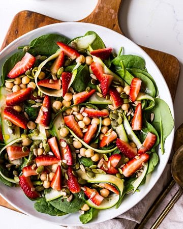 Strawberry, chickpea and spinach salad in a wide bowl on wooden chopping board