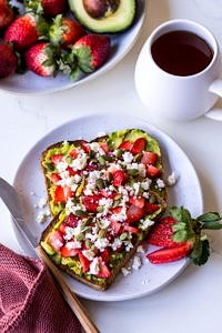 Strawberry avocado toast with a cup of tea