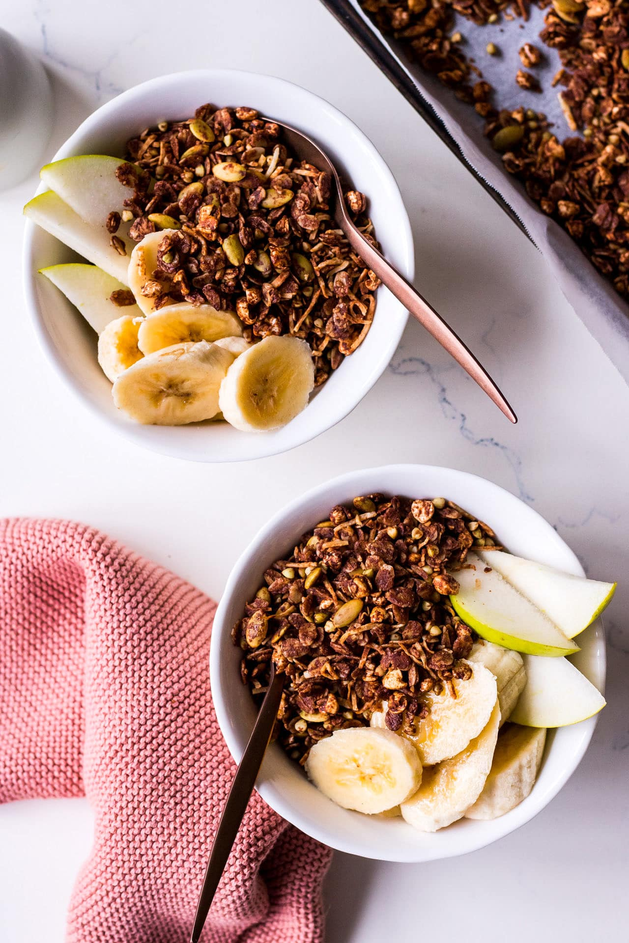 Two white cereal bowls close up spaced diagonally with banana, pear, chocolate olive oil granola and bronze spoons