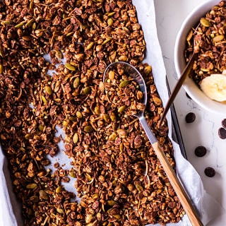 Tray of chocolate olive oil granola with a spoon, small bowl to the side