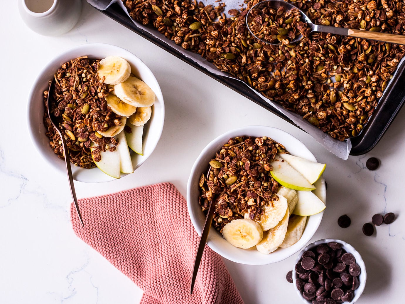 Two small white bowls with pear, banana, chocolate granola and bronze spoons, surrounded by a small cup of chocolate chips and tray of chocolate granola