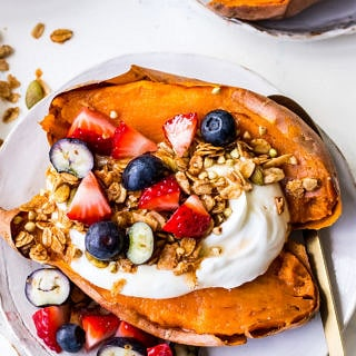 Baked sweet potato on white plate topped with Greek yoghurt, berries and granola