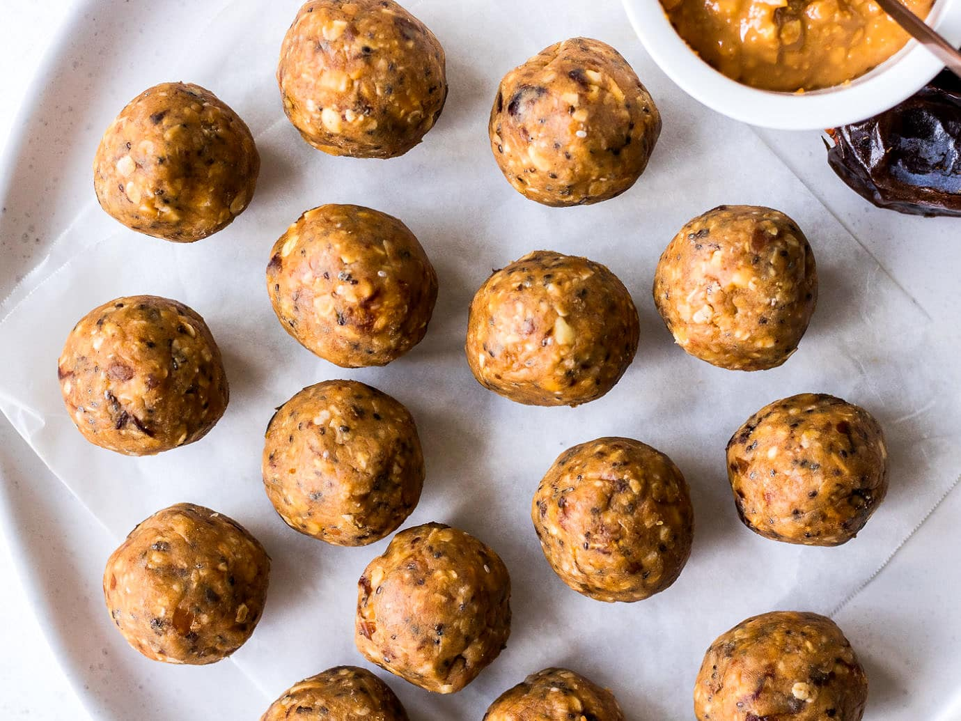 Peanut butter date energy balls arranged on a white ceramic plate