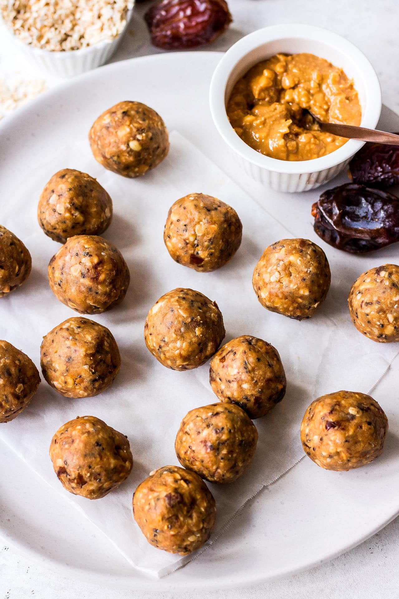 White plate with energy balls, crunchy peanut butter, medjool dates and quick oats arranged