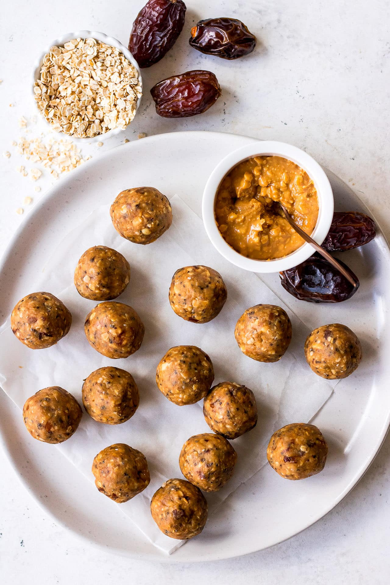 Top down view of a plate of peanut butter energy balls with a mini bowl of crunchy peanut butter, medjool dates and quick oats arranged around them