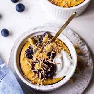 Vanilla mug cake in white ramekin with blueberries, yoghurt and shredded coconut, blue napkin and blueberries