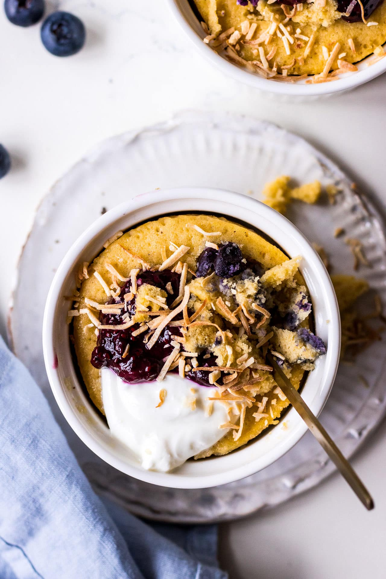 Top down view of a vanilla mug cake in white ramekin topped with blueberries, yoghurt and shredded coconut with a blue napkin and gold teaspoon