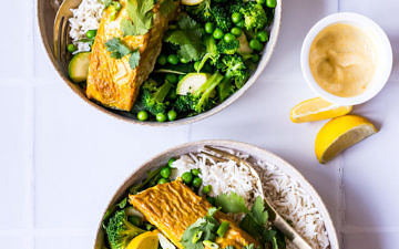 Two bowls with white rice, green vegetables and curry baked salmon garnished with lemon and coriander