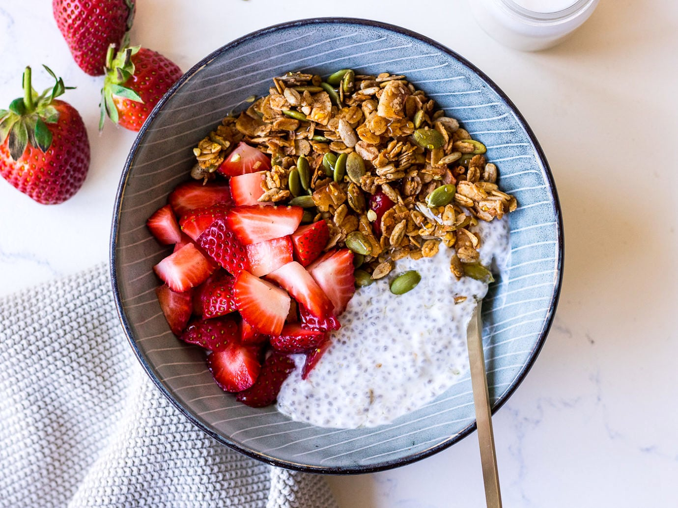 Blue bowl with chia pudding, chopped strawberries and granola, small gold spoon