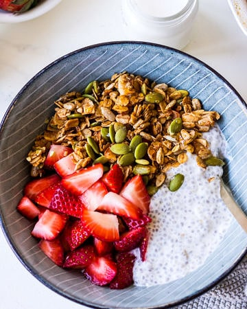 Healthy Cinnamon Granola bowl with sliced strawberries and chia pudding